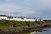 Watched over by the old lighthouse a row of whitewashed cottages with the brightly-painted lintels and doors which are typical of the island