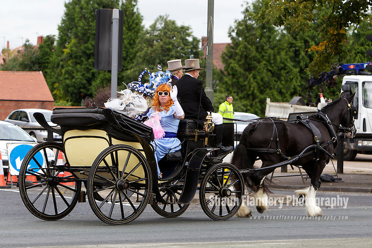 Pix: Shaun Flannery/shaunflanneryphotography.com...COPYRIGHT PICTURE>>SHAUN FLANNERY>01302-570814>>07778315553>>..13th September 2012..Dave Parkes and Ian Spowart (ginger) dressed as 'ladies' arrive by horse drawn carriage at Doncaster Racecourse ahead of Ladies Day. The duo are hoping for glory in the Best Dressed Lady competition.
