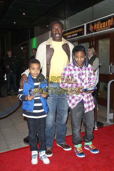 Linford Christie & guests.Hans Klok's 'The Houdini Experience' Press Night at the Peacock Theatre, London, England..February 28th 2012.full length jeans denim yellow blue purple check shirt top kids children.CAP/ROS.©Steve Ross/Capital Pictures