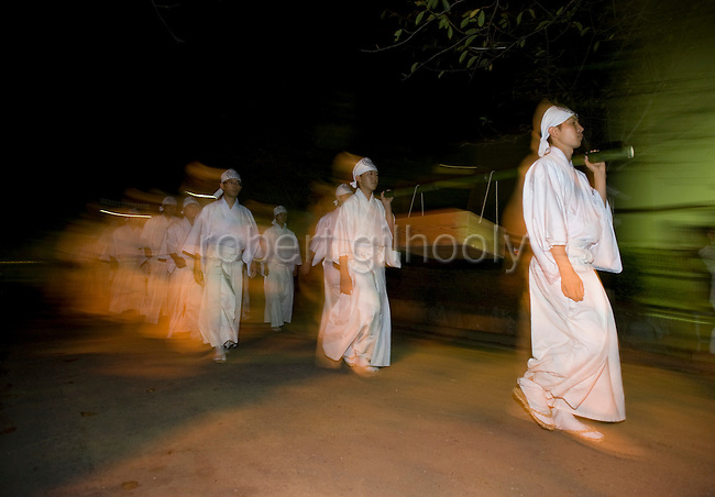 """Shrine priests and officials make their way along the Dankazura approach road of the Tsurugaoka Hachimangu shrine on their way to Yuhigahama beach to perform a rite known as """"hamaorisai"""" at the start of the 3-day Reitaisai festival in Kamakura, Japan on  14 Sept. 2012.  Photographer: Robert Gilhooly"""