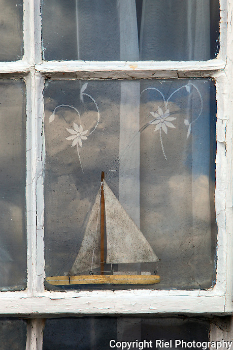 "A toy or model boat in an aged window, a flawed curtain and the reflection of clouds reminds me of sailing to the wilds things (aka ""Where the Wilds Things Are"" by Maurice Sendak.)"