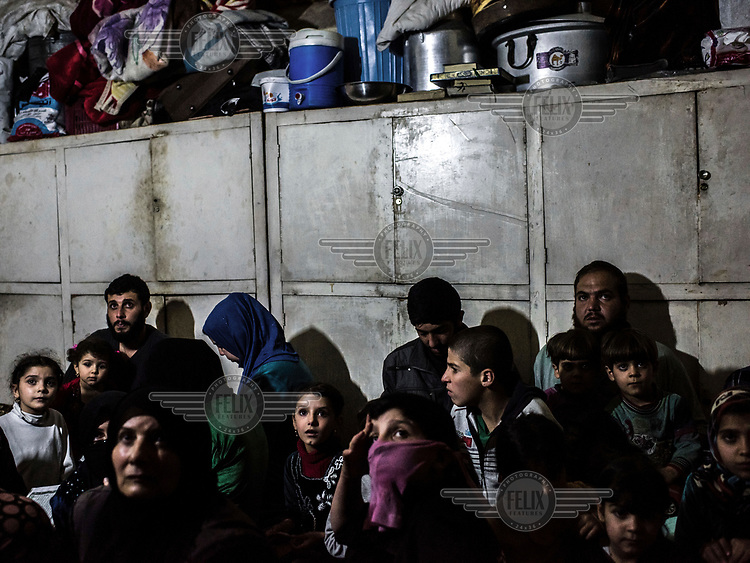Families look up anxiously while they hide in a basement as fighting between ISIS militants and pro-government forces rages above them on the front line in the al Thawra neighbourhood of western Mosul.