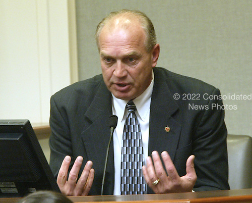 Roger Thomson, a sergeant in the Homicide and Sex Section of the Montgomery County, Maryland Police Department, gestures during his testimony in the trial of sniper suspect John Allen Muhammad in Virginia Beach Circuit Court in Virginia Beach, Virginia on November 9, 2003. <br /> Credit: Tracy Woodward - Pool via CNP