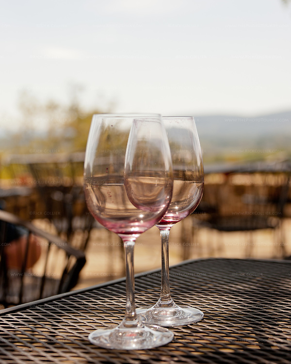 Used and emptied wine glasses have been left on a table on the patio at Hillsborough Vineyards.