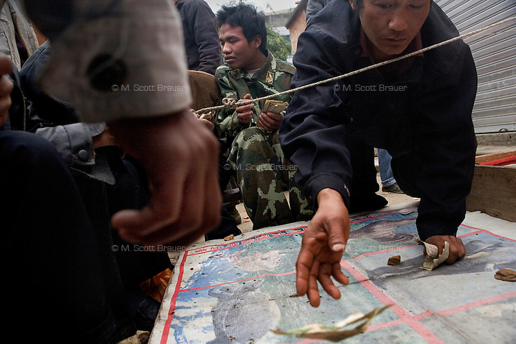 Men gamble on market day in Pangzhihua Village, Yuanyang County, Yunnan Province, China.