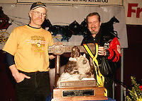 2006 Iditarod winner Jeff King and Mr. Rod Udd stands before the winners trophy