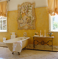 The wall of this elegant bathroom has been painted with a trompe l'oeil tiled picture above the free-standing bath
