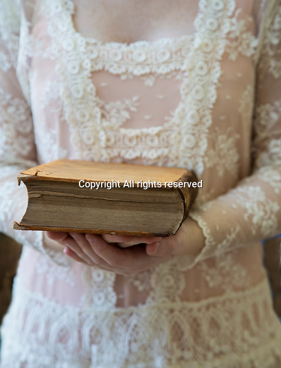 A young lady holds an old book.