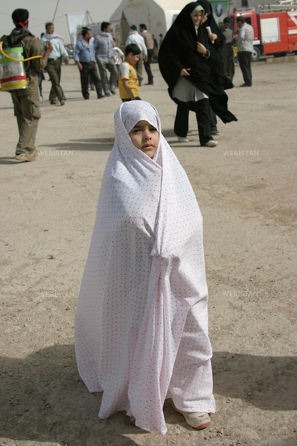 Iran. Khuzistan. Mars 2009. Shalamcheh. La premi&egrave;re ligne de la guerre Iran-Irak. (Pendant laquelle il y a eu pres de1 million de morts). Une petite fille voil&eacute;e d'un Chadore sur les lieux de Shalamcheh.<br /> Pr&egrave;s de la fronti&egrave;re irakienne. Chaque ann&eacute;e, lors des c&eacute;l&eacute;brations de la f&ecirc;te de Norouz, le nouvel an iranien, des milliers d'iraniens de tout le pays, appel&eacute;s &quot;Rahian-e Noor&quot; (la caravane de lumi&egrave;re en persan), aid&eacute;s par des organisations gouvernementales, se rassemblent sur les anciens champs de batailles pour comm&eacute;morer leurs proches tomb&eacute;s comme soldat ou bassidji. La prise en charge totale des frais de d&eacute;placement et logement par l'&eacute;tat, font de ce p&egrave;lerinage un &eacute;vement touristique pris&eacute; des familles les plus mod&egrave;stes. La guerre Iran-Iraq fut l'un des conflits arm&eacute;s les plus meutriers du dernier quart du vingti&egrave;me si&egrave;cle, faisant environs un million de victimes.<br /> Iran. Kurdistan. Mars 2009. Shalamcheh. Frontline zone of the Iran-Irak war (during which almost 1 million people died). A veiled little girl in Shalamcheh.<br /> Near the remains of Iran-Iraq War (1980-1988) frontline zone, close to the Iraqi border. Every year, during the celebration of Nowrooz, the Iranian new year, thousands of Iranians from all over the country, called &quot;Rahian-e Noor&quot; (Caravan of light in Persian), helped by state organizations, gather on former battle fields to commemorate their loved ones who died as soldiers or Basijis. All expenses of this pilgrimage being paid by the State, makes it a favored touristic destination for  families of humble background. The Iran-Iraq War was one of the deadliest armed conflicts of the last quarter of the twentieth century, leaving one million victims.