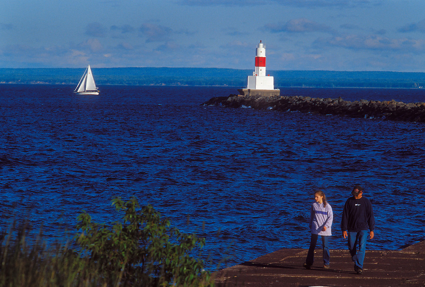 A sailboat passes the Upper Harbor breakwater light as tourists stroll the breakwater in Marquette, Mich.