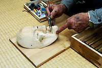 Hizawa Koun measuring a female mask with calipers. The mask has been over carved and built up again using sawdust mixed with resin on the right cheek.