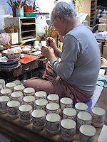 A man paints teacups by hand in the old tradition