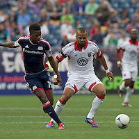 New England Revolution midfielder Clyde Simms (19) passes the ball as DC United forward Maicon Santos (29) pressures. In a Major League Soccer (MLS) match, DC United defeated the New England Revolution, 2-1, at Gillette Stadium on April 14, 2012.