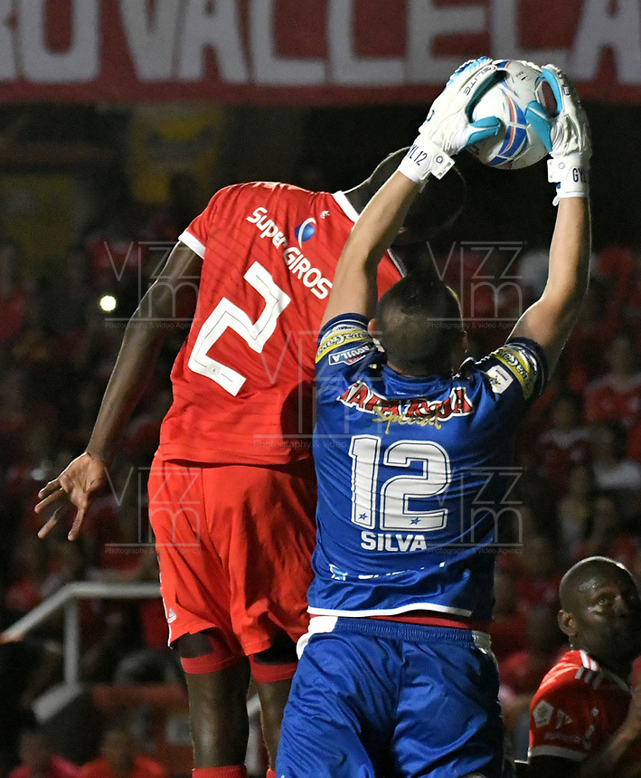 CALI - COLOMBIA - 10 -  02  -  2018: Danilo Arboleda (Izq.) jugador de America, salta a disputar el balón con Joel Silva (Der.) portero de Deportes Tolima, durante partido entre America de Cali y Deportes Tolima, de la fecha 2 por la Liga Aguila I 2018 jugado en el estadio Pascual Guerrero de la ciudad de Cali. / Danilo Arboleda (L) of player of America, jumps to vies for the ball with Joel Silva (R) goalkeeper of Deportes Tolima, during a match between America de Cali and Deportes Tolima, of the 2nd date for the Liga Aguila I 2018 at the Pascual Guerrero stadium in Cali city. Photo: VizzorImage / Luis Ramirez / Staff.