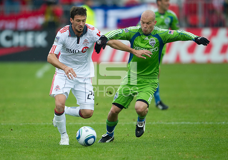 25 April 2010:   Toronto FC midfielder Martin Saric #25 and Seattle Sounders midfielder Freddie Ljungberg #10 battle for a ball during a game between the Seattle Sounders and Toronto FC at BMO Field in Toronto..Toronto FC won 2-0....