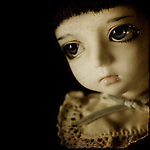 Close up of a dolls face with large brown eyes