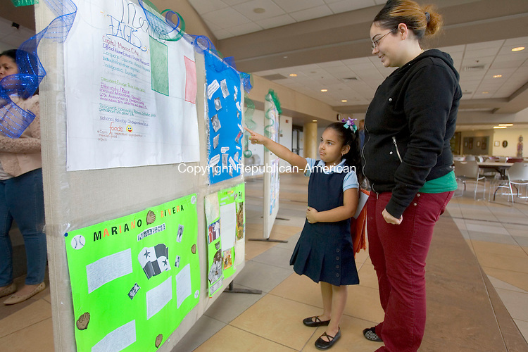 WATERBURY CT. 27 October 2014-102714SV04-Jazlene Greponne, 5, and her mom Christina Cuevas of Waterbury check out the Hispanic Month posters during a show at a ceremony wrapping up Hispanic Heritage Month for the Waterbury schools held at Naugatuck Valley Community College in Waterbury Monday.<br /> Steven Valenti Republican-American