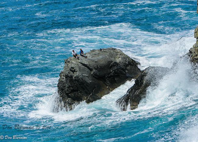 Two men fish from a hughe coastal rock below the Via Dell'Amore (Path of Love) between Roimaggio and Manarola, Cinque Terre, Italy.