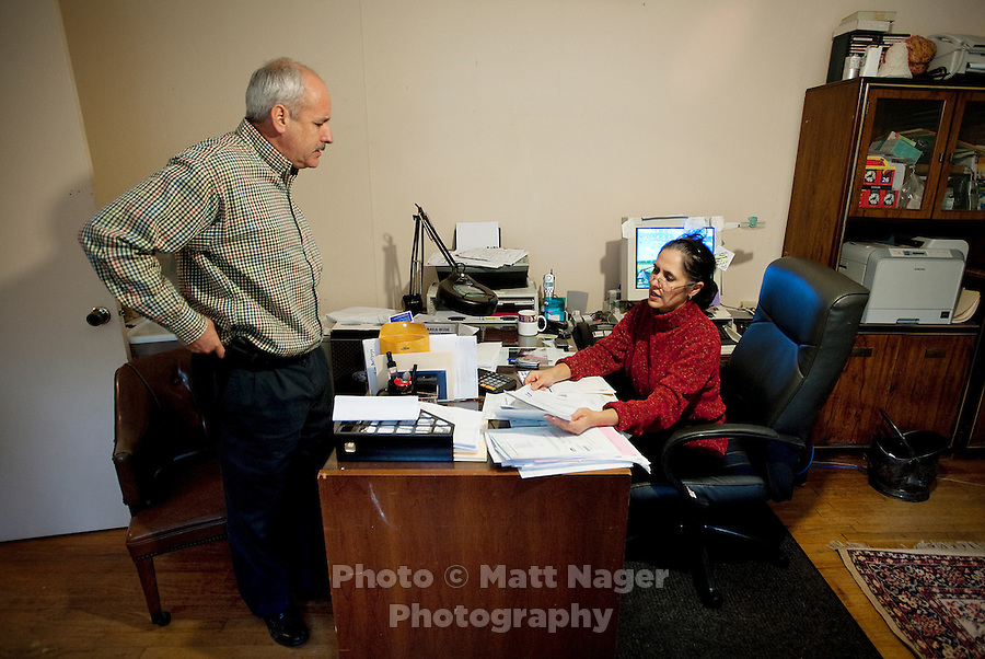 John Woodard (cq) and his wife, Martha Woodard (cq), at their home office in Laredo, Texas, US, Thursday, Dec. 10, 2009. The couple were forced to move their office from the apartment complex they own and manage, to their home in order to rent out the original space to make more money. Because of the slumping economy, John is looking into getting another job to make ends meet. Martha, a native Spanish speaker from Mexico, is learning English, in part, to help take over managing their apartment business and be able to answer phone calls in English. ..PHOTOS/ MATT NAGER