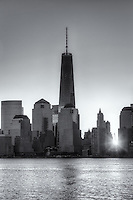 The sun rises over lower Manhattan as the Freedom Tower (1 World Trade Center) stands tall nearby in the World Trade Center complex, in New York City.
