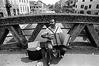 """Milano, un mendicante suona la fisarmonica su un ponte del Naviglio Grande. Sul cartone la scritta: """"Ho tre figli e sono malato di leucemia"""" --- Milan, a beggar playing accordion on the Naviglio Grande canal. Written on the cardboard:""""I have three children and i'm ill with leukemia"""""""