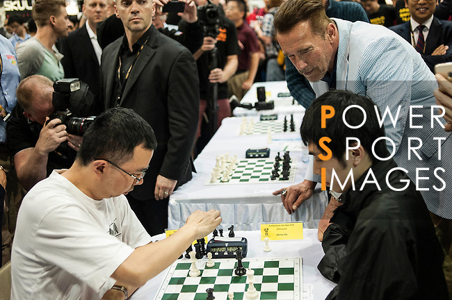 US actor and former California governor, Arnold Schwarzenegger observes two players of  chess during the officiation of the Arnold Classic Asia Multi-Sport Festival in Hong Kong. Photo by Marcio Machado / Power Sport Images