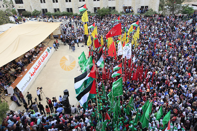 Palestinian supporters of the Islamic Hamas movement and Fatah movement attend a rally prior to the Student Council elections at Birzeit University, on the outskirts of the city of Ramallah in the West Bank on May 6, 2014. The Student Council elections , which will take place on May 7, will pit student supporters of the top two political movements Hamas and Fatah, days after the intra-Palestinian reconciliation agreement. On April 23, the Palestine Liberation Organisation (PLO) -- internationally recognised as the sole representative of the Palestinian people -- and the Islamist Hamas which rules the Gaza Strip signed a reconciliation agreement. Photo by Issam Rimawi