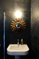 Brazilian black slate flooring is used for the walls of a modern bathroom where a gilt sun-ray mirror hangs above a pedestal washbasin.