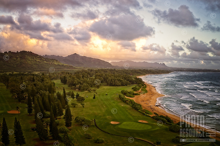 "Aerial view of the sunrise over Wailua Golf Course, along the ""Coconut Coast"" of eastern Kaua'i, with the Sleeping Giant mountain in the distance."