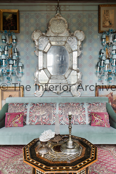 In the blue reception room, there is a customised blue armchair and printed cushions, with upholstery designed by Serdar Gülgün, in front stands an Ottoman-inspired coffee table inlaid with mother of pearl and tortoise shell.The walls have antique Venetian Murano lights and a striking Venetian mirror reflects the light.