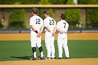 (L-R) Joe Napolitano (12), Jimmy Redovian (23) and Joey Rodriguez (7) stand for the National Anthem prior to the game against the High Point Panthers at Wake Forest Baseball Park on April 2, 2014 in Winston-Salem, North Carolina.  The Demon Deacons defeated the Panthers 10-6.  (Brian Westerholt/Four Seam Images)