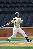 Garrett Kelly (28) of the Wake Forest Demon Deacons follows through on his swing against the Marshall Thundering Herd at Wake Forest Baseball Park on February 17, 2014 in Winston-Salem, North Carolina.  The Demon Deacons defeated the Thundering Herd 4-3.  (Brian Westerholt/Four Seam Images)