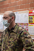 "Switzerland. Canton Ticino. Rivera. Monte Ceneri military base. Due to the spread of the coronavirus (also called Covid-19), the Federal Council has categorised the situation in the country as ""extraordinary"". The army was called upon to provide logistical support and to offer its skills in terms of medical assistance (ambulances, field hospital, tents, nurses,..). The militia soldiers from medical troops were called by the Swiss army for the first time since World War II. Under the country's militia system, professional soldiers constitute a small part of the military and the rest are conscripts or volunteers aged 19 to 34 (in some cases up to 50).  A soldier waits to wash his hands before entering the refectory. The bald man wears a mask in front of his mouth. On the wall, the Coronavirus poster explains how to prevent from getting the disease. The measures are: Keep your distance, wash your hands thoroughly, avoid shaking hands, cough and sneeze into a tissue or the crook of your arm, stay at home if you have fever, always call ahead before going to the doctor's or the emergency department. Monte Ceneri is a mountain pass in the canton of Ticino. It connects the Magadino plain and the Vedeggio valley across the Prealps. 2.04.2020 © 2020 Didier Ruef"