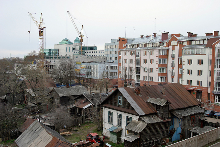 Tver, Russia, 30/04/2004..Old wooden houses surrounded by new apartments and shops in the city centre.