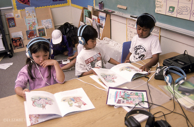 1st grade latino kids in bilingual Spanish-Engiish class using audio equipment to help with reading    San Rafael CA