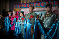 A Mongolian bride (2nd-L) and family members greet guests during a traditional wedding ceremony in Damao Banner, Inner Mongolia, China, October 2014.