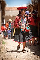 Quechua woman in traditional dress, carries child, Chinchero Town Sunday Market, Cusco region, Peru, South America