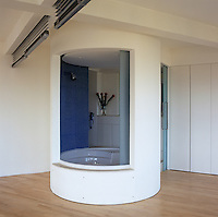 In this bathroom the shower is enclosed in a circular pod lined with ultramarine mosaic tiles