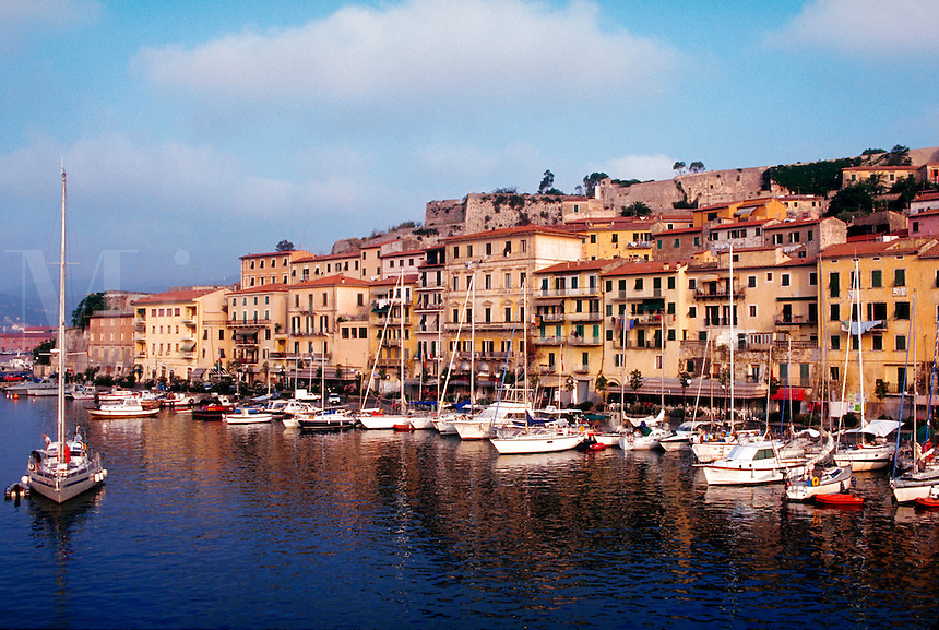 Elba-Portoferraio, Italy. Mediterranean seaport scene overview of Elba. Old apartment and waterfront buildings and boats.