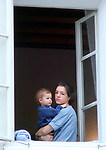 "A mother looks out on a Salzburg street in the ""altstad"" as she holds her young son."