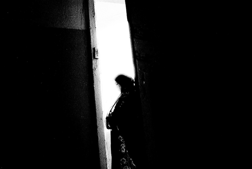 Noor, an Iraqi refugee from Baghdad, stands in the doorway of her small home in Amman, Jordan, September 2009. Photo: Ed Giles.