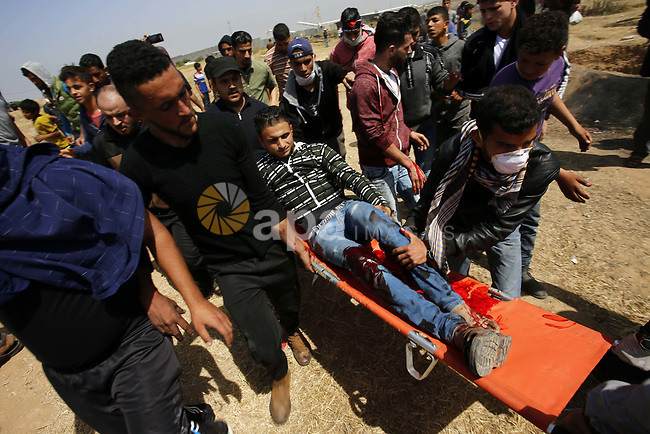 A wounded Palestinian protester is evacuated during clashes with Israeli security forces at the Israel-Gaza border in a tent city protest demanding the right to return to their homeland, in east of Gaza city on April 6, 2018. Photo by Ramadan Elagha