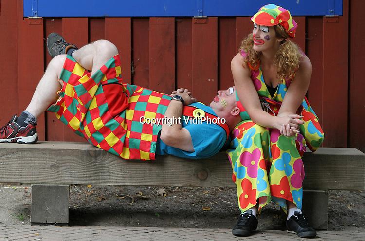 Foto: VidiPhoto..RHENEN - Bekaf en niet zo vrolijk mee. Twee clowns begeleiden maandag de speelweek van kinderen uit Elst (U) in Ouwehands Dierenpark in Rhenen en hebben het halverwege de dag wel gehad. Even uitrusten dus. Gelukkig zijn ze er niet alleen voor de kinderen, maar ook voor elkaar.