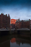 Sun setting on the waterways of the Speicherstadt old town. Customs houses, warehouse and dock areas of Hamburg, Germany.