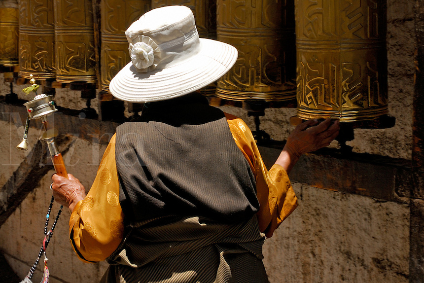 Tibetan Buddhist with hand-held prayer wheel and mala beads circumambulates rows of prayer wheels on the Barkhor pilgrim circuit around the Jokhang Temple, Lhasa, Tibet.