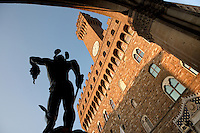 Low angle view from behind of statue of Perseus holding the Head of Medusa, 1554, by Benvenuto Cellini, and Palazzo Vecchio, Piazza de la Signoria, Florence, Tuscany, Italy, pictured on June 8, 2007, in the late afternoon. The statue was commissioned by Cosimo I de Medici and has recently been restored. The Palazzo Vecchio, begun in 1299, was designed by Arnolfo di Cambio (1245-1302). Florence, capital of Tuscany, is world famous for its Renaissance art and architecture. Its historical centre was declared a UNESCO World Heritage Site in 1982. Picture by Manuel Cohen.