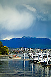 Boats at Coal Harbour, Vancouver, B.C, Canada in early summer. Buildings and a mountain are in the background. Dramatic clouds look menacing on the horizon.