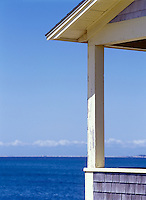 Detail of porch, expanse of water, blue sky, crisp sun. North Truro, Massachusetts on Cape Cod.
