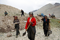 China started building a controversial 67-mile &quot;paved highway fenced with undulating guardrails&quot; to Mount Qomolangma, known in the west as Mount Everest, to help facilitate next year's Olympic Games torch relay./// Tibetan women get back to work on the road to EBC. <br /> Tibet, China<br /> July, 2007