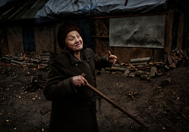 Popasna, eastern Ukraine Nov. 2017.<br /> <br /> Svetlana Nikolaevna Lebed, 62. <br /> <br /> In the ongoing conflict between Ukraine and pro-Russian separatists&rsquo;, several Grad rockets (&lsquo;Grad' meaning &lsquo;hail&rsquo;) hit her home, and the surrounding area on 14/2/2015. Coming from separatists&rsquo; positions only fifteen minutes after a ceasefire had ended between the two sides.<br /> <br /> She was in bed when the rockets struck and is lucky to be alive, but the attack caused extensive damage to her house. With an outside temperature of -8c and no-where else to go, she was forced to stay where she was.<br /> <br /> The walls are cracked and although she has had some minor repairs done to the roof it still leaks severely. The local administration gave her two pieces of tarpaulin for the roof, but despite pleas from a neighbour on her behalf, they wouldn&rsquo;t give her enough to cover the whole roof. <br /> <br /> She bought the property eighteen years ago but doesn&rsquo;t have the official papers for its purchase and so can&rsquo;t qualify for help to rebuild it. <br /> <br /> She cannot afford the electric for heating or fuel for cooking, although sometimes a neighbour from the next village will bring her some hot food. She doesn't receive any support from anyone else.<br /> <br /> Without the necessary repairs to the building, she fears it will fall down and so will be forced to go into an old people&lsquo;s home. &lsquo;I ask God to let me live longer for the sake of my dogs'.